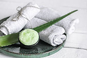 Spa composition with a natural care product with aloe and towels close up.