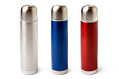 Three stainless steel thermoses red, blue and metal isolated on white background.