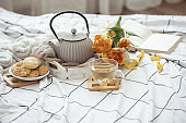 Spring home composition in bed with a cup of tea, cookies, a teapot, a book and a bouquet of flowers.