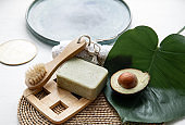 Spa composition with natural soap, brush and avocado close up.