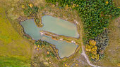 Little lake or pond of unusual shape with a beautiful autumn nature photographed from above with a drone.