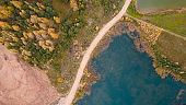 Little lake or pond of unusual shape with a beautiful autumn nature and mud road photographed from above with a drone.