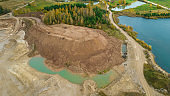 Little lake or pond of unusual shape with a beautiful autumn nature and gravel piles photographed from above with a drone.