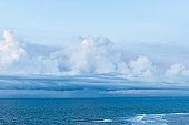 Bali beach scene - turquoise Indian ocean and cloudy sky.