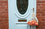 Reusable string bag from environmentally friendly materials with citrus fruits and blank card hanging on the door handle. Local farmer healthy food delivery. Zero-waste, plastic-free lifestyle