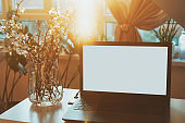 A home workplace with white screen laptop for mockup, blooming branches in a vase on the desk with room interior background in sunset light. Freelance, working from home, online learning, home office
