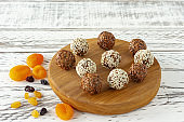 Homemade natural vegan chocolate truffle with cacao and coconut flakes on wooden desk on white background