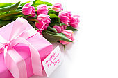 Mother's day gift and pink tulips on white background