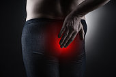 Man suffering from hemorrhoids, anal pain on black background