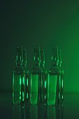 Biotechnology and Science. Medicine and Pharmacology concept. transparent ampoules set in green light.Organic natural cosmetics concept.Ampoules with solution for injection.Health and beauty