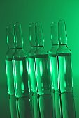 Biotechnology and Science. Medicine and Pharmacology .Glass transparent ampoules in green light.Organic natural cosmetics concept.Ampoules with solution for injection.Health and beauty