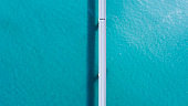 """Running in parallel with the car.""""Tsunoshima Bridge"""" in Yamaguchi Prefecture, Japan. A marine road bridge with a superb view. Taken with a drone on a sunny day. The road over the sea is very beautiful."""