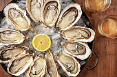 Oysters close-up. A dozen of raw oysters with wine and lemon
