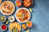 Mexican food, an overhead flat lay. Nachos, tacos, and other snacks
