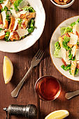 Caesar salad with wine and lemons, top flat lay shot