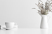 White book, cup of a coffee and a lavender in a vase on a white table. Flat lay with blank copy space.