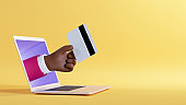 3d illustration. African cartoon character hand sticking out the laptop screen, holding plastic credit card. Business financial clip art isolated on yellow background. Internet banking service
