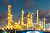 Industrial plant at night with sky background.