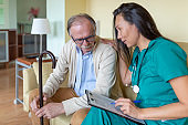 Sick Old Man is Receiving Advice From Nurse in Home Visit.