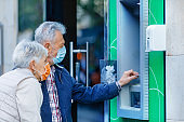 Senior Couple with Face Masks is Using an ATM Machine.