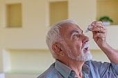 A Senior Man with Cataract or Conjunctivitis is Using an Eye Drops at Home.