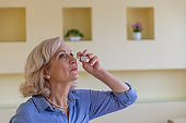 An Older Woman is Using Eye Drops for Better Vision.