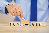 Hand holding home with Buy or Rent, real estate concept.