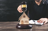 Man with judge gavel and house model. Real Estate Lawyer