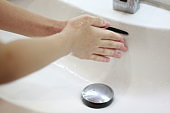 A woman's hand washing in wash bowl  to prevent from coronavirus or covid 19 infection during pandemic.Selective focus at hand .closeup shot.