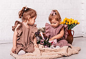 Two pretty girls in beautiful dresses open a box with a gift in a room with flowers