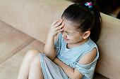 Depressed little girl sitting on the sofa