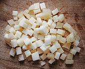 Diced Italian pecorino cheese  on cutting board made of olive wood