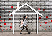 A young girl in a gray pullover, jeans, sneakers and with a backpack walking along the street. House symbol, wall. The concept of safe quarantine during the COVID-19 coronavirus pandemic. Stay at home
