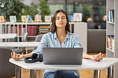 Beautiful happy young woman or student female meditates at workplace