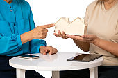 Asia satisfied senior woman pointing house model selection on senior real estate agent hand on white background