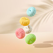 Flying colorful halloween pumpkins on pastel background, holiday tropical decoration. 3d render