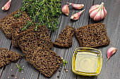 Pieces of black bread, thyme sprigs, butter in glass bowl and garlic on table.