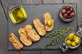 Pieces of bread, sprigs of thyme. Jars of olives and glass bowl of oil.
