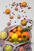 Persimmon, apples and lemon in reusable mesh bag