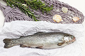 Raw fish trout on paper. Sprigs of rosemary on mesh bag.