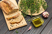 Pieces of bread on cutting board. Thyme sprigs in wicker plate.
