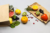 Fruits in paper bag. Persimmon, kiwi, grapes and lemon on paper