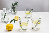 Three glasses with lemon and sprig of thyme.