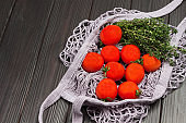 Red tomatoes and thyme twigs in natural reusable mesh bag