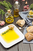 Olive oil in white plate with slice of bread and sprig of thyme.