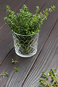 Thyme sprigs in glass. Thyme on table.