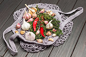 Red chili, thyme sprigs, garlic in natural reusable mesh bag.