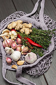 Red chili, thyme sprigs, garlic and ginger root in natural reusable mesh bag