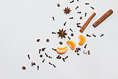 Cinnamon sticks and star anise, spice cloves, tangerine slices are scattered on table