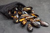 Mussels are scattered from reusable bag on table.